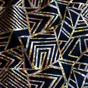 "Gold Geometric Stretch fabric features bold geometric designs in ""Broken Glass"" hologram foil on black stretch base fabric for a stunning contrast effect."