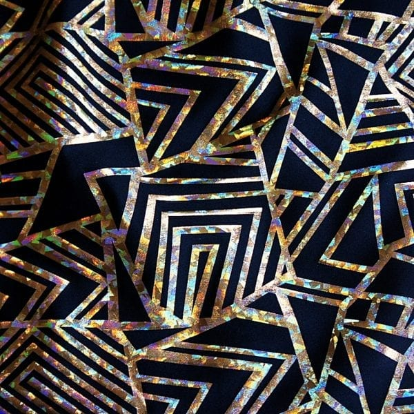 """Gold Geometric Stretch fabric features bold geometric designs in """"Broken Glass"""" hologram foil on black stretch base fabric for a stunning contrast effect."""