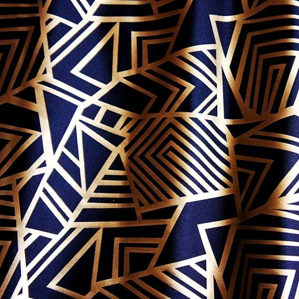Geometry Matte Gold Geometric fabric features bold geometric designs in a sleek matte gold foil on black stretch base fabric for a stunning contrast effect. - SOLID STONE FABRICS, INC.