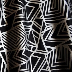 Geometry Matte Silver Geometric fabric features bold geometric designs in a sleek matte silver foil on black stretch base fabric for a stunning contrast effect.  - SOLID STONE FABRICS, INC.