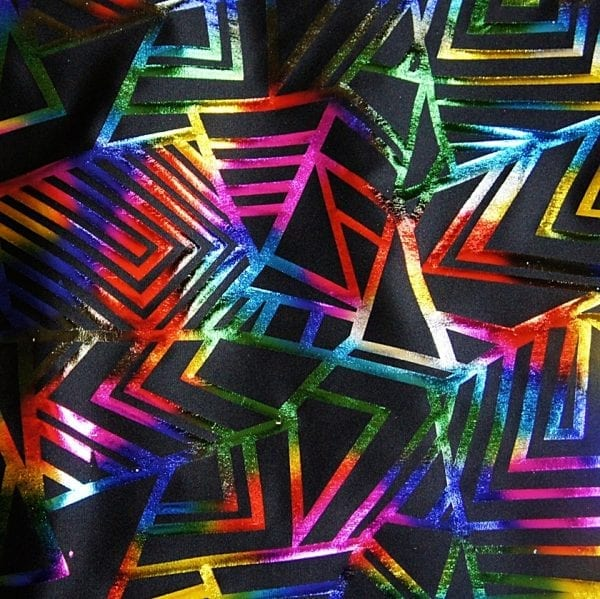 Multi Colored Geometric fabric features bold rainbow geometric foil designs on black stretch base fabric for a stunning contrast effect.
