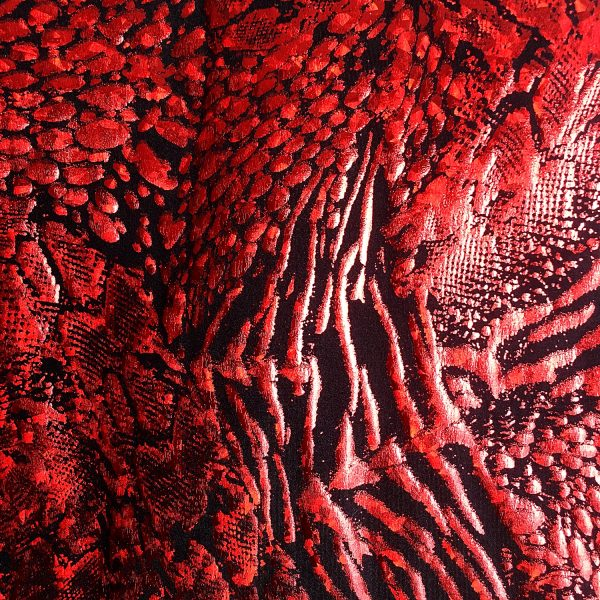 Red animal print hologram fabric featuring black stretch base fabric topped with red shattered glass holographic foil in multiple animal prints for brilliant shine and sparkle.