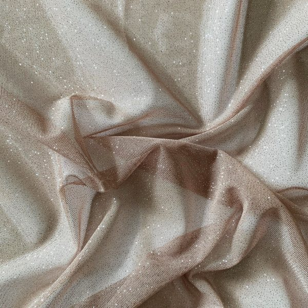 Nude Silver Glitter Mesh fabric features all over silver glitter on 2-way stretch nude polyester mesh making it ideal for both semi-fitted and draped garments.