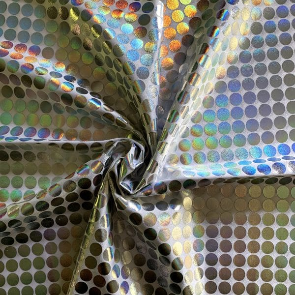 Large Holographic dot fabric featuring white 4-way stretch base fabric topped with silver holographic foil dots measuring 1.5 cm/.59 in in diameter.
