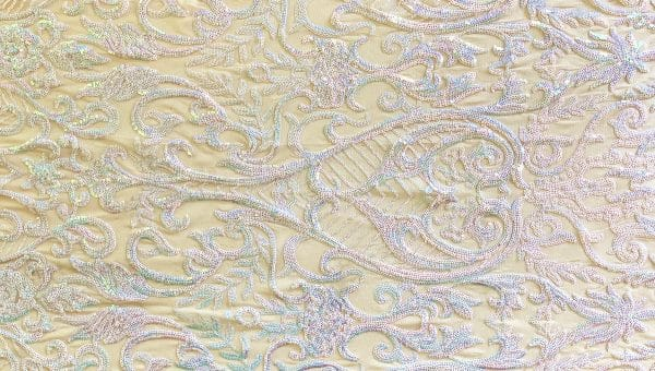 Sophisticated - White/Nude features elegant floral white iridescent sequin designs on nude stretch mesh base fabric for a glamorous look! Luxury white iridescent sequin mesh fabric featuring 2-way stretch and excellent draping characteristics makes this an ideal fabric choice for both semi-fitted and loose fitting garments.