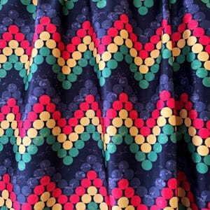 Rasta Print Fabric featuring red, yellow, green, grey and black dots in a zig zag repeating pattern